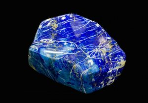 Polished Lapis Lazuli pebble isolated on black.